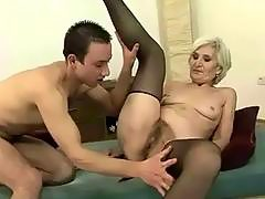 Granny in black stockings enjoys sex with a boy